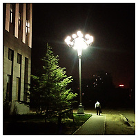 A man walking down a street at night in Beijing, China.