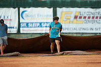 Javier Martinez (54) (Catawba Valley CC) of the Mooresville Spinners helps pull the tarp prior to the exhibition game against the Race City Bootleggers at Moor Park on July 23, 2020 in Mooresville, NC. (Brian Westerholt/Four Seam Images)