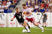 Jan Gunnar Solli (8) of the New York Red Bulls is defended by Daniel Woolard (21) of DC United. The New York Red Bulls defeated DC United 3-2 during a Major League Soccer (MLS) match at Red Bull Arena in Harrison, NJ, on June 24, 2012.