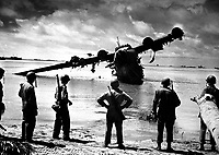 U.S. Army troops pause for a look at a Japanese seaplane during the battle of Makin.  The plane was under repair in the lagoon when the invasion started.  The Japanese used it as a machine gun nest until American fliers took care of it.  November 1943.  (Coast Guard)<br /> Exact Date Shot Unknown<br /> NARA FILE #:  026-G-3000<br /> WAR & CONFLICT BOOK #:  1320
