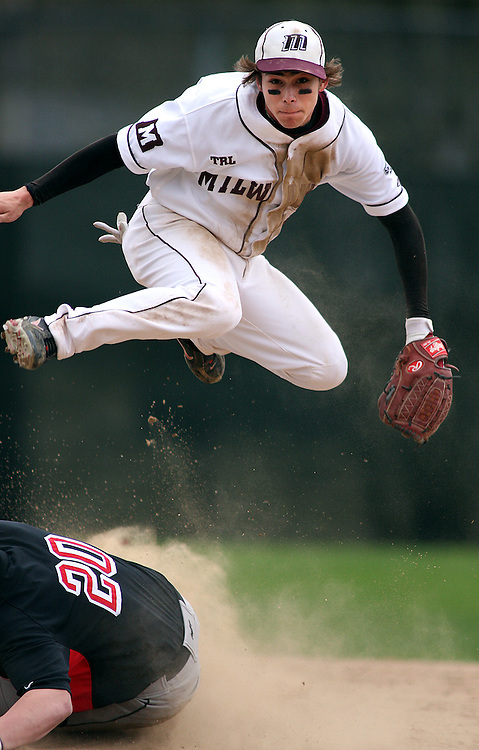 Milwaukie's Adam Frank leaps over a sliding Clackamas Jack Goodwin at second base after making a throw to first base for a double play in the third inning.
