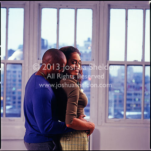 African American couple embracing with windows in background<br />