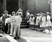 Boys and girls in lines preparing to enter their school. 1950's.<br />