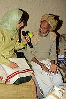 Muscat, Oman, Arabian Peninsula, Middle East - Woman TV Journalist Interviewing Male Weaver, Muscat Festival.