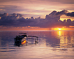 Bora Bora, French Polynesia   <br /> Setting sun and tropical evening clouds reflect on the calm waters of Bora Bora lagoon with outrigger anchored off Matira beach