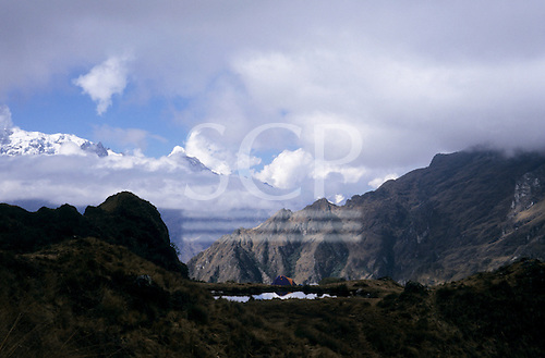 Inca Trail, Peru. View across to the smaller of the two Black Lakes with tents behind and snowcapped peaks in distance.