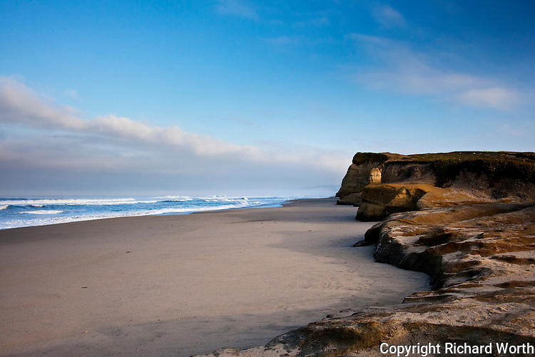 Sky, clouds, ocean and shoreline combine to draw lines to the distant, tall bluff at Pomponio State Beach on Califonia's coast south of San Francisco.