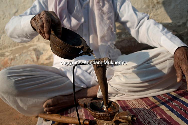 A bishnoi man making Amal(the opium drink) at his home. Bishnoi people are fond of opium. This also their ritual to greet visitors with opium drink. Jodhpur, Rajasthan, India. Arindam Mukherjee