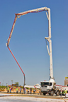 Workers lay concrete slabs using a concrete pump in Abu Dhabi city center/centre.   United Arab Emirates.
