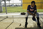Baseball player Travis Sheffield, 15, on the bench during an Reviving Baseball Inner city (RBI) I league game at the renovated Algin Sutton Recreation Center field in Los Angeles, CA.