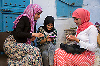 Chefchaouen, Morocco.  Young Arab Women Checking their Cell Phones.