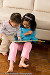 16 month old toddler boy looking at picture book with 8 year old sister vertical