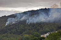 Smoke is still smouldering after a fire in Kilvey Hill, above house in the Saint Thomas area of Swansea, Wales, UK. Friday 17 May 2019