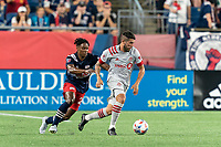 FOXBOROUGH, MA - JULY 7: Alejandron Pozuelo #10 of Toronto FC dribbles as DeJuan Jones #24 of New England Revolution defends during a game between Toronto FC and New England Revolution at Gillette Stadium on July 7, 2021 in Foxborough, Massachusetts.