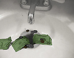 Close-up of American dollar currency drowning down the sink depicting wrong investment