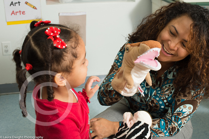 Preschool 3 year olds female teacher and girl using puppets to talk