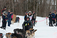 Kaci Murringer and team run past spectators on the bike/ski trail near University Lake with an Iditarider in the basket and a handler during the Anchorage, Alaska ceremonial start on Saturday, March 7 during the 2020 Iditarod race. Photo © 2020 by Ed Bennett/Bennett Images LLC