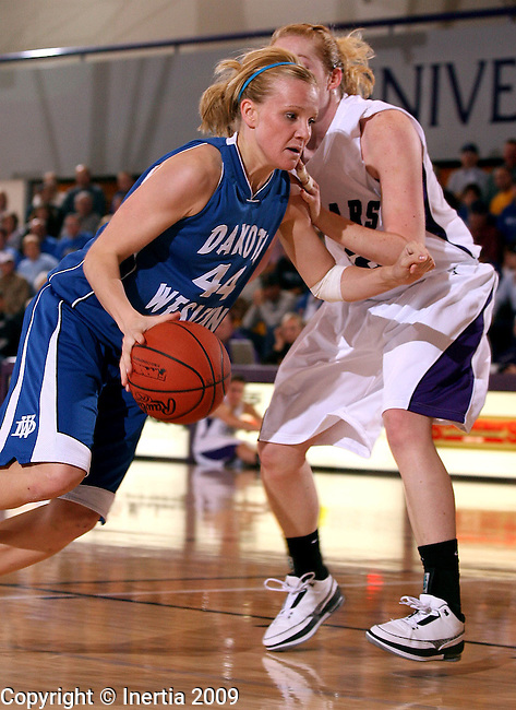 SIOUX FALLS, SD - DECEMBER 9:  Ashley Mailey #44 of Dakota Wesleyan drives against Elizabeth Hildreth #52 of the University of Sioux Falls in the first half of their game Wednesday night at the Stewart Center in Sioux Falls. (Photo by Dave Eggen/Inertia)