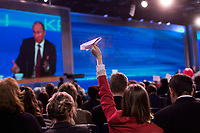 A reporter uses a paper airplane to try to get the attention of Russian president Vladimir Putin during Putin's annual press conference in Moscow, Russia. The press conference lasted 5 hours.