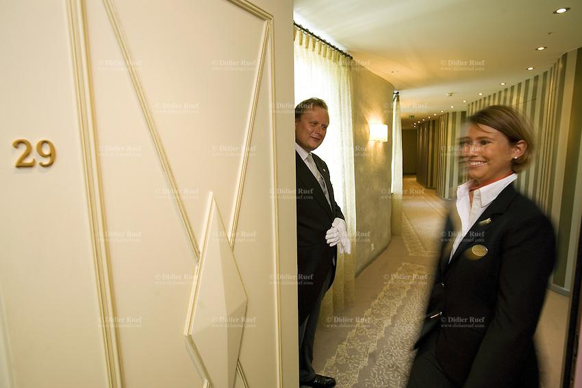 Switzerland. Canton Graubünden. St. Moritz. Hotel Carlton.  Stefan Kleinat (L), butler, and Franziska Titze (R) welcome a guest to his suite. © 2008 Didier Ruef