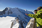 Visitors in the upper terrace of Aiguille Du Midi with the peak of Mont Blanc in the background. Chamonix. France