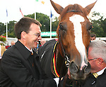 Horse Racing - Leopardstown Racecourse - Irish Champion Stakes.Aidan O'Brien who trianed the first four winners including the The Tattersalls Millions Irish Champion Stakes celebrates with Cape Blanco's groom at Leopardstown Racecourse in Dublin.