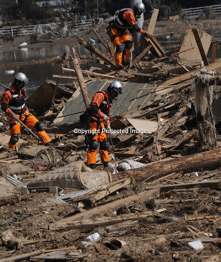 Search and rescue teams look through the remains of houses in the devasted  town of Natori, after the Tsunami devastated the entire pacifc coastline of Japan after the earthquake and tsunami devastated the area Sendai, Japan.<br /><br />photo by Richard Jones/ sinopix