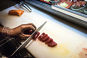 A chef slices the sustainably caught  yellow fin tuna for the guests during the sunday brunch at the restaurant of the Macro Polo Hotel in Ortigas Center, Metro Manila in the Philippines. <br /> Photo: Sanjit Das/Panos for Greenpeace