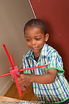 3 year old boy plaing with wood cube and stick construction talking to self vertical