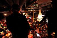 Two plain clothed police officers watch a crowd a a busy restaurant.<br /> <br /> Stig Gaustad og Morten Haukeland fra Sentrum Politistasjons etteretningsavdeling følger med på utelivet i Oslo sentrum. . (Foto:Fredrik Naumann/Felix Features)