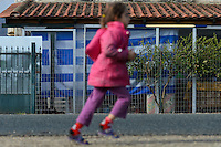 Pictured: A young girl runs past a house draped with the Greek flag Tuesday 01 March 2016<br /> Re: Thousands of migrants, still stranded at the Greek FYRO Macedonian border in Idomeni, Greece