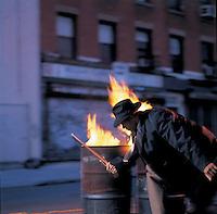 Man in suit swinging nightstick in front of fire barrels
