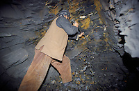 A miner digging by hand in a hunt of Emeralds in a 200 meters deep cave at 4000 meters high, in the Panshir valley.