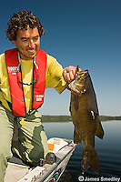 Fisherman holding a large bass he caught fishing.