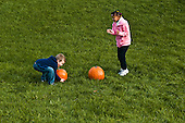 MR / Schenectady, NY. Girl (6, African-American) claps while boy (6) picks up a pumpkin. One of a series of photographs where two children count pumpkins from one to five so could be used for a counting spec. MR: Lus1, Joh18. ID: AK-ICP. © Ellen B. Senisi