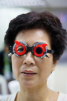 Thailand. Bangkok. Tha Tian Community Center. A woman with chinese origin wears a pair of glasses in order to check her field of vision. Eyes examination during an Ophthalmology sight checkup. Once a month, a Health care program financed by the Bangkok Metropolitan Administration (BMA) offers a free medical checkup by a group of trained doctors and nurses. Tha Tian is a community located in the downtown area and in the center of the urban historic district, called Koh Rattanakosin. 01.04.09 © 2009 Didier Ruef