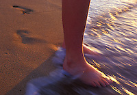 Young woman standing on beach in late afternoon with water flowing over her feet