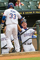 Round Rock Express manager Steve Buechele (22) greets first baseman Carlos Pena (33) on the dugout steps after he homered during the Pacific Coast League baseball game against the Fresno Grizzlies on June 22, 2014 at the Dell Diamond in Round Rock, Texas. The Express defeated the Grizzlies 2-1. (Andrew Woolley/Four Seam Images)