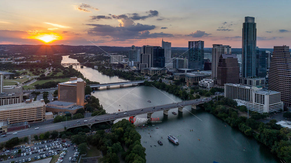Aerial view of sunset falling on the downtown Austin skyline as bat watchers gather on the Congress Avenue Bridge to watch the bats take flight.