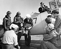 """The Photo squadron personal, planes, and cameras equipment.  Students with instructor checking out on the F-56 aerial camera with its 20"""" lens.  This can be used for either hand held oblique shots or vertical mosaic mapping photos.  It weighs 43 lbs; can take220 exposures on a roll.  Location: NAS Pensacola, Florida."""