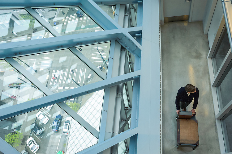 A library worker moves materials in the open floor plan of the Seattle Central Public Library.
