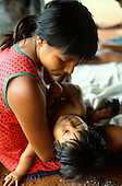 A-Ukre Village, Brazil. Payngroti, a Kayapo woman, holding her child in her arms. Xingu Indian Reserve.