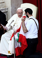 A Lebanese priest Georges Breidi holding Lebanon's flag kneels next to Pope Francis (L) making a statement about the situation in Lebanon, during the first limited public audience at the San Damaso courtyard in The Vatican on September 2, 2020 during the COVID-19 infection, caused by the novel coronavirus.<br /> UPDATE IMAGES PRESS/Isabella Bonotto<br /> <br /> STRICTLY ONLY FOR EDITORIAL USE