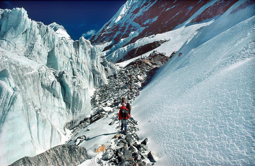 .High-altitude trekking group ascend a rock corridor through the Drolambo Glacier, below the Tesi Lapcha pass, Rolwaling region, Nepal Himalaya...