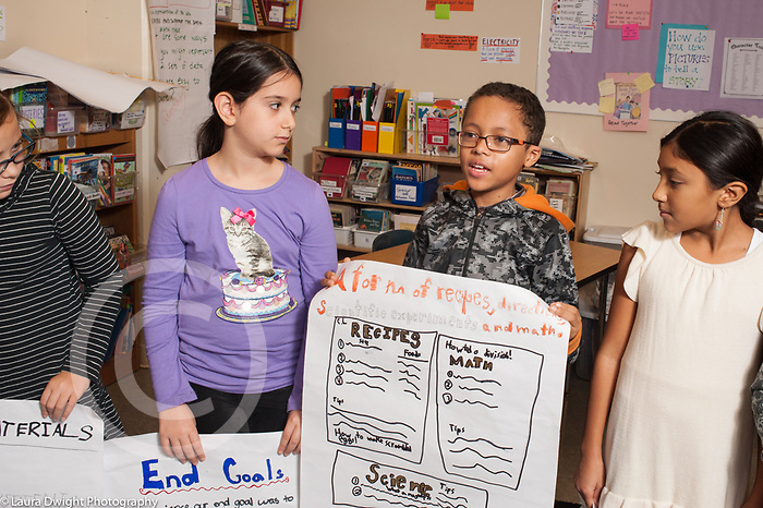 Education Elementary Grade 4 grammar presentation for the school one boy and three girls with their posters, boy presenting on his project