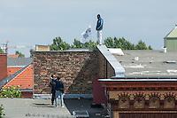 """Fluechtlingsprotest auf dem Dach der Gerhard-Hauptmann-Schule in der Ohlauer Strasse in Berlin-Kreuzberg.<br /> Seit dem 24. Juni 2014 haben harren Fluechtlinge und deren Unterstuetzer auf dem Dach der Gerhard-Hauptmann-Schule aus. Sie hatten sich geweigert dem sog. """"Freiwilligen Umzug"""" zu folgen, der vom Gruenen Bezirksstadtrat Hans Panhoff angeordnet worden war. Die Polizei war bei der als """"Umzug"""" geschoenten Raeumung mit gezogenen Maschinenpistolen angerueckt.<br /> Baustadtrat Panhoff hat am 1. Juli 2014 die polizeiliche Raeumung des Schulgebaeudes beantragt. Einige der Fluechtlinge haben angekuendigt, im Fall der Raeumung vom Dach zu springen. """"Wir haben nichts mehr zu verlieren!"""" sagen sie.<br /> Die Polizei hat seit dem 24. Juni mit ueber 1.000 Beamten saemtliche Strassen um die Schule abgeriegelt. Anwohner duerfen nur nach Personalienfeststellung in ihre Wohnungen, Geschaefte und Gewerbe koennen keine Kundschaft mehr empfangen. Anwohner die gegen das Vorgehen der Polizei protestieren werden von Beamten drangsaliert, geschlagen und verletzt. Mehrere Personen, darunter auch Kinder mussten zum Teil mit Kieferbruch ins Krankenhaus.<br /> Im Bild: Ein Fluechtling redet auf dem Dach mit zwei Journalisten.<br /> 2.7.2014, Berlin<br /> Copyright: Christian-Ditsch.de<br /> [Inhaltsveraendernde Manipulation des Fotos nur nach ausdruecklicher Genehmigung des Fotografen. Vereinbarungen ueber Abtretung von Persoenlichkeitsrechten/Model Release der abgebildeten Person/Personen liegen nicht vor. NO MODEL RELEASE! Don't publish without copyright Christian-Ditsch.de, Veroeffentlichung nur mit Fotografennennung, sowie gegen Honorar, MwSt. und Beleg. Konto: I N G - D i B a, IBAN DE58500105175400192269, BIC INGDDEFFXXX, Kontakt: post@christian-ditsch.de<br /> Urhebervermerk wird gemaess Paragraph 13 UHG verlangt.]"""