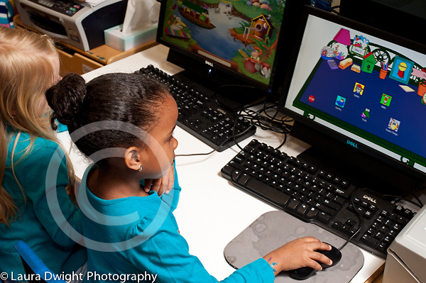 Preschool classroom 4 year olds two girls sitting side by side playing learning games on computers