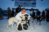 Martin Buser hugs his leaders at the finish line as a crow gathers arount in Nome on Thursday March 19, 2015 during Iditarod 2015.  <br /> <br /> (C) Jeff Schultz/SchultzPhoto.com - ALL RIGHTS RESERVED<br />  DUPLICATION  PROHIBITED  WITHOUT  PERMISSION