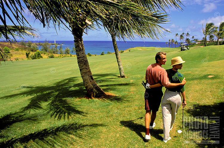 Couple walk with theirs arms around each other on the green turf of a golf course on Oahu.