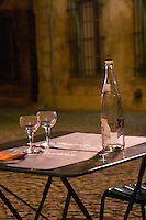 The restaurant l'Epicerie in Avignon. A lone table with two chairs, an empty bottle of water and two glasses after a couple have left having finished dinner. Avignon, Vaucluse, Provence, Alpes Cote d Azur, France, Europe